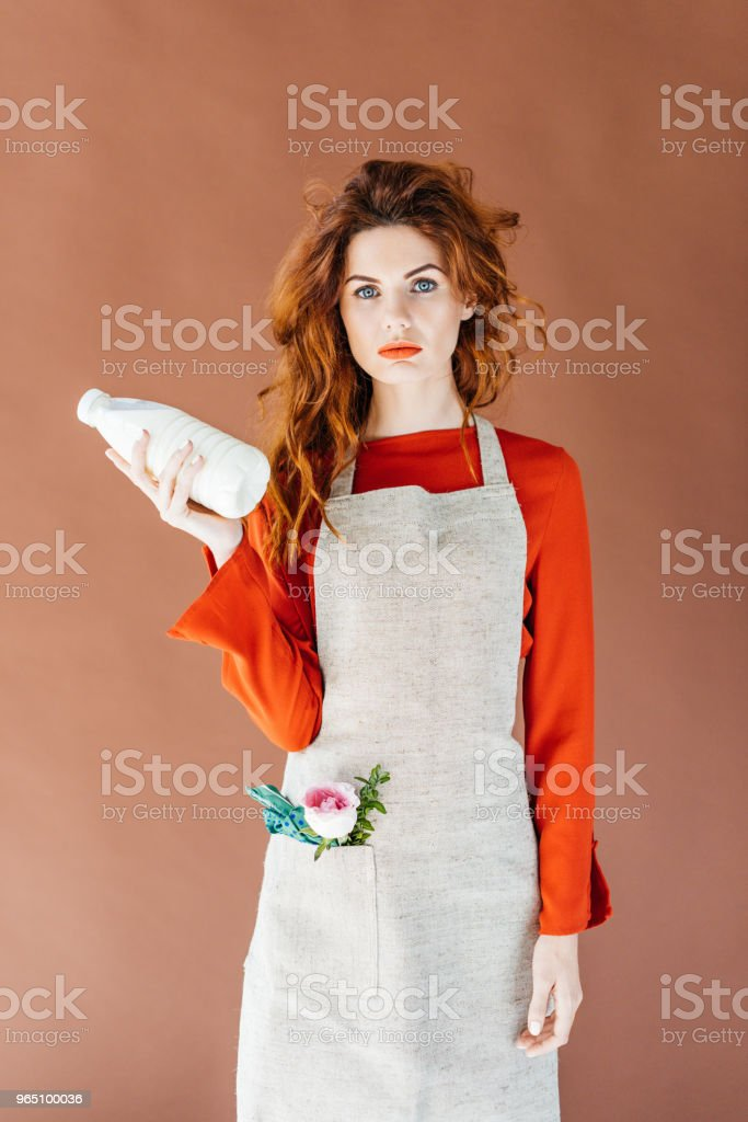 Woman with long red hair in apron holding milk bottle isolated on brown background zbiór zdjęć royalty-free