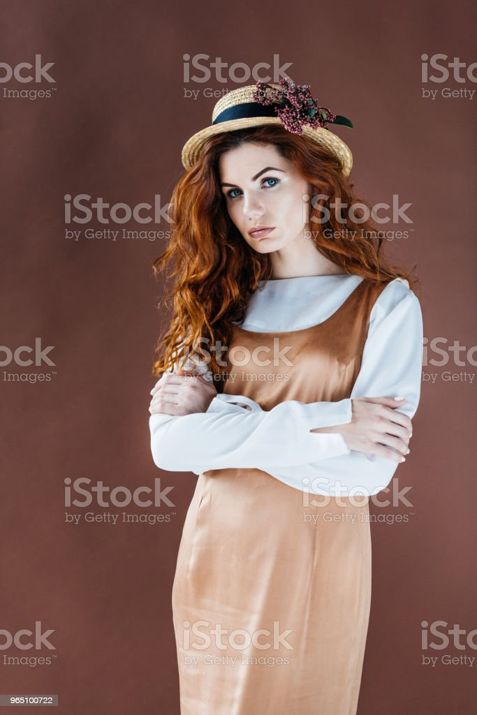 Woman with long red hair in beige dress and straw hat isolated on brown background zbiór zdjęć royalty-free