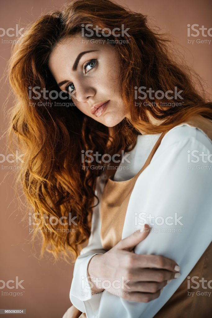 Woman with long red hair in beige dress looking at camera isolated on brown background zbiór zdjęć royalty-free