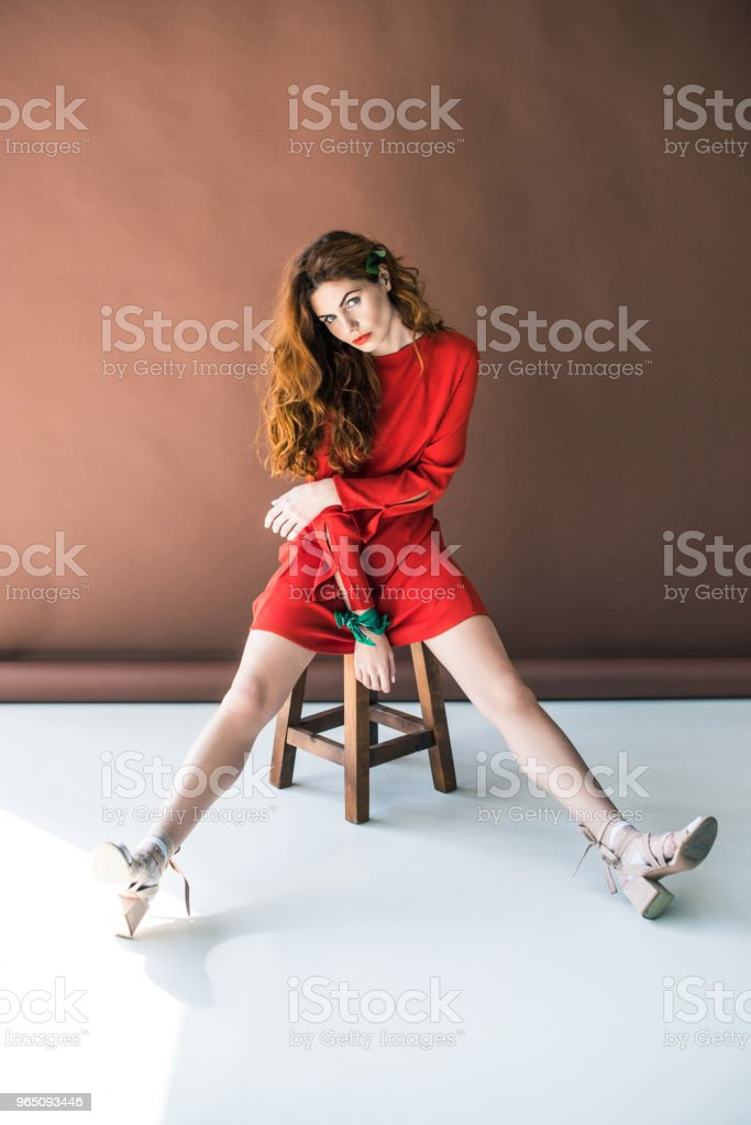 Woman with long red hair in red dress posing on wooden stool royalty-free stock photo