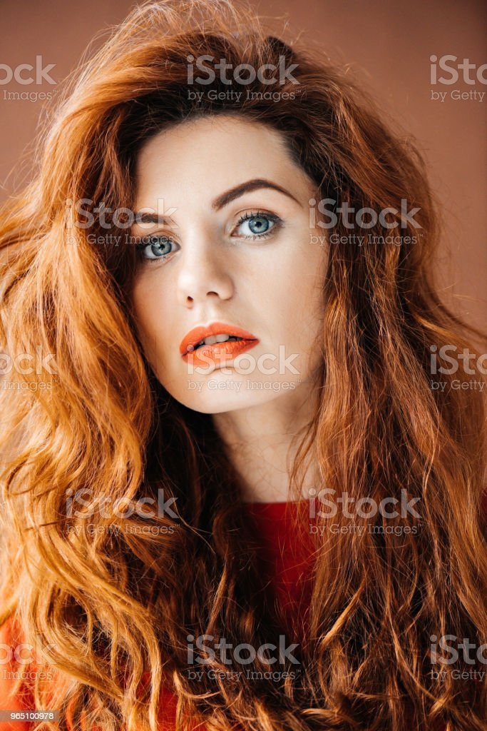 Woman with long red hair isolated on brown background royalty-free stock photo