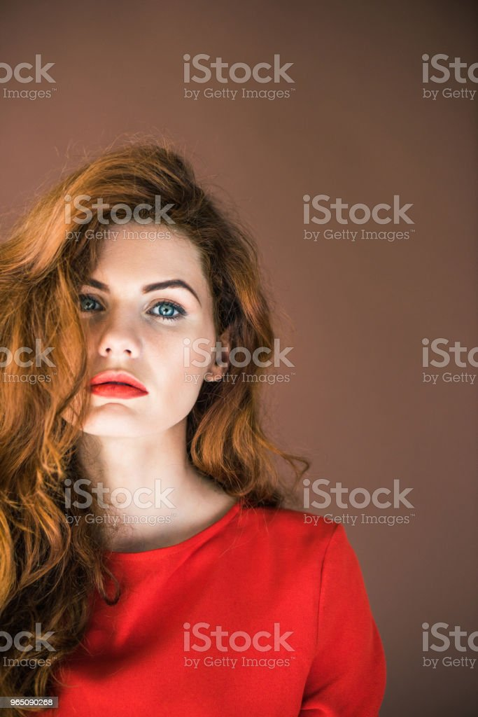 Woman with long red hair looking at camera isolated on brown background royalty-free stock photo