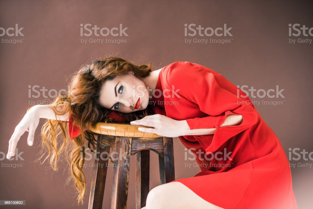 Woman with long red hair lying on wooden stool isolated on brown background royalty-free stock photo