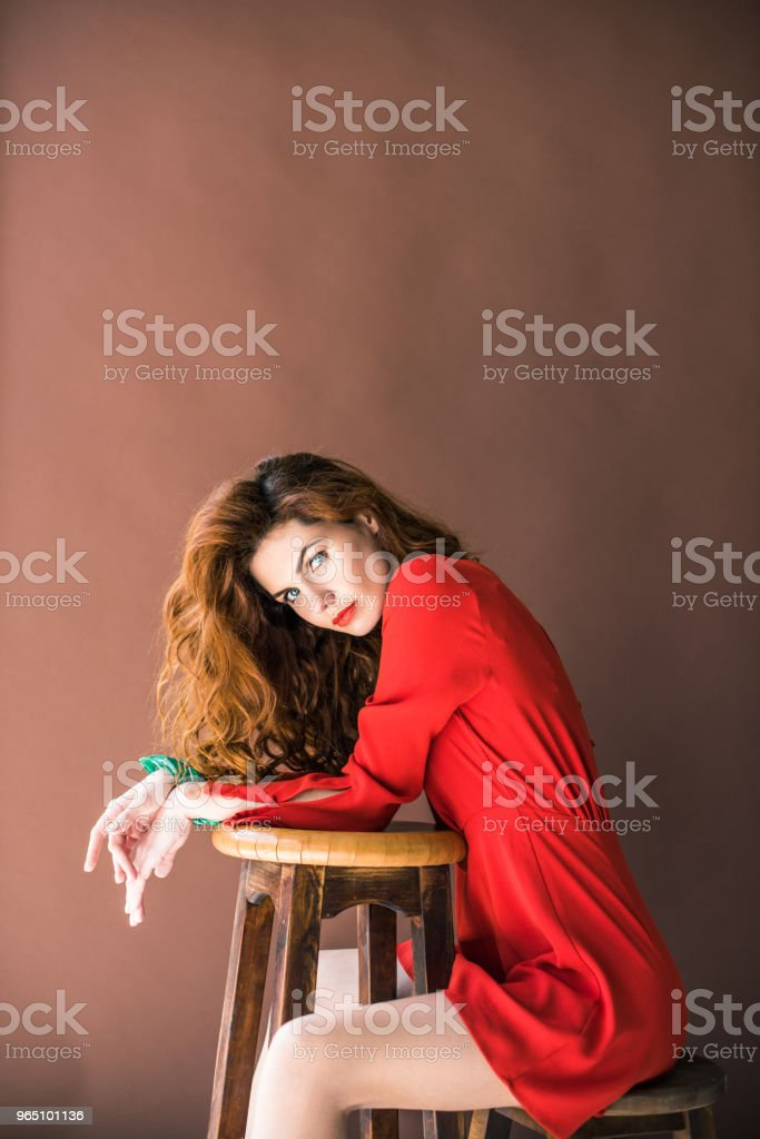 Woman with long red hair sitting on chair by stool isolated on brown background zbiór zdjęć royalty-free