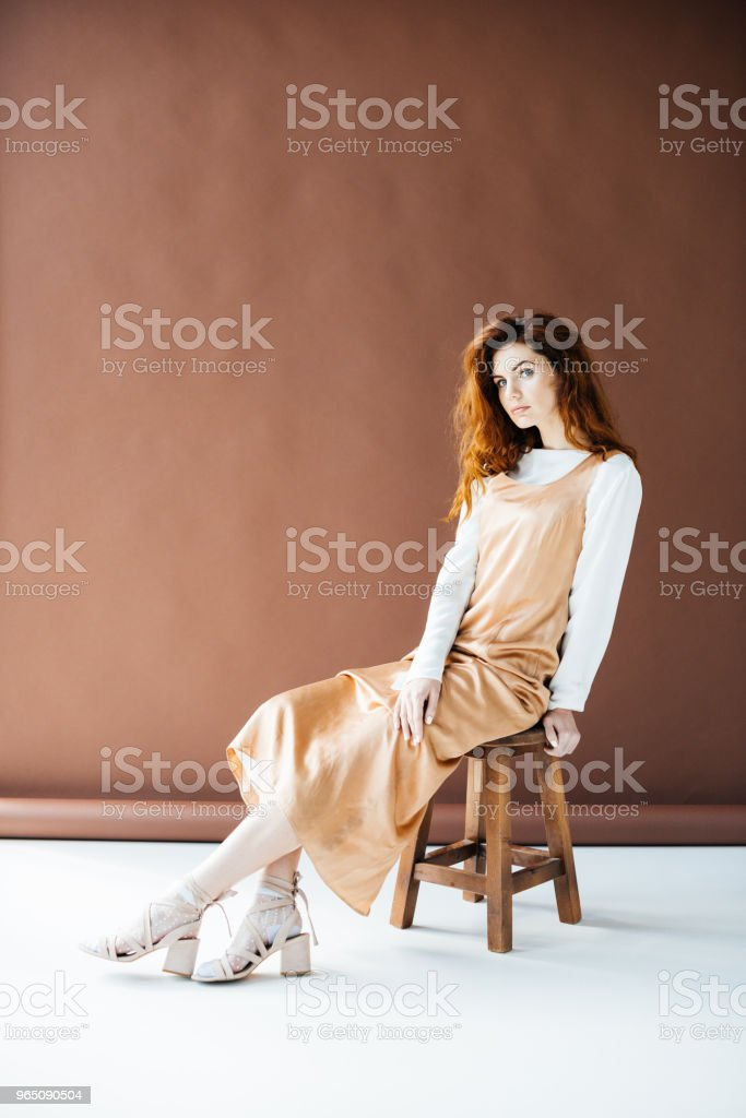 Woman with long red hair  sitting on wooden stool royalty-free stock photo