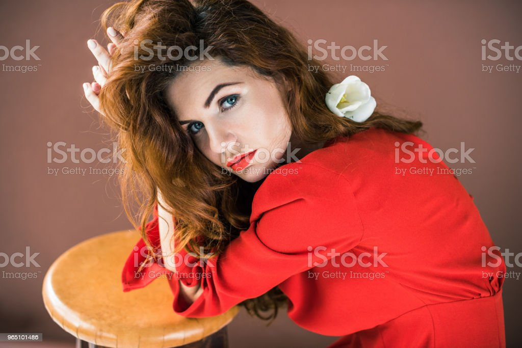 Woman with long red hair with tulip flower leaning on stool isolated on brown background zbiór zdjęć royalty-free