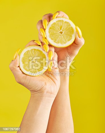 Woman's hands with beautiful yellow nails, holding two slices of lemons against yellow background