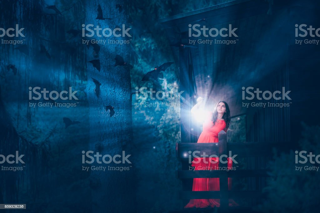 Woman with magic light in a dark forest stock photo