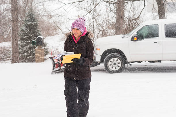 woman with mail in a snow storm - strooigoed stockfoto's en -beelden