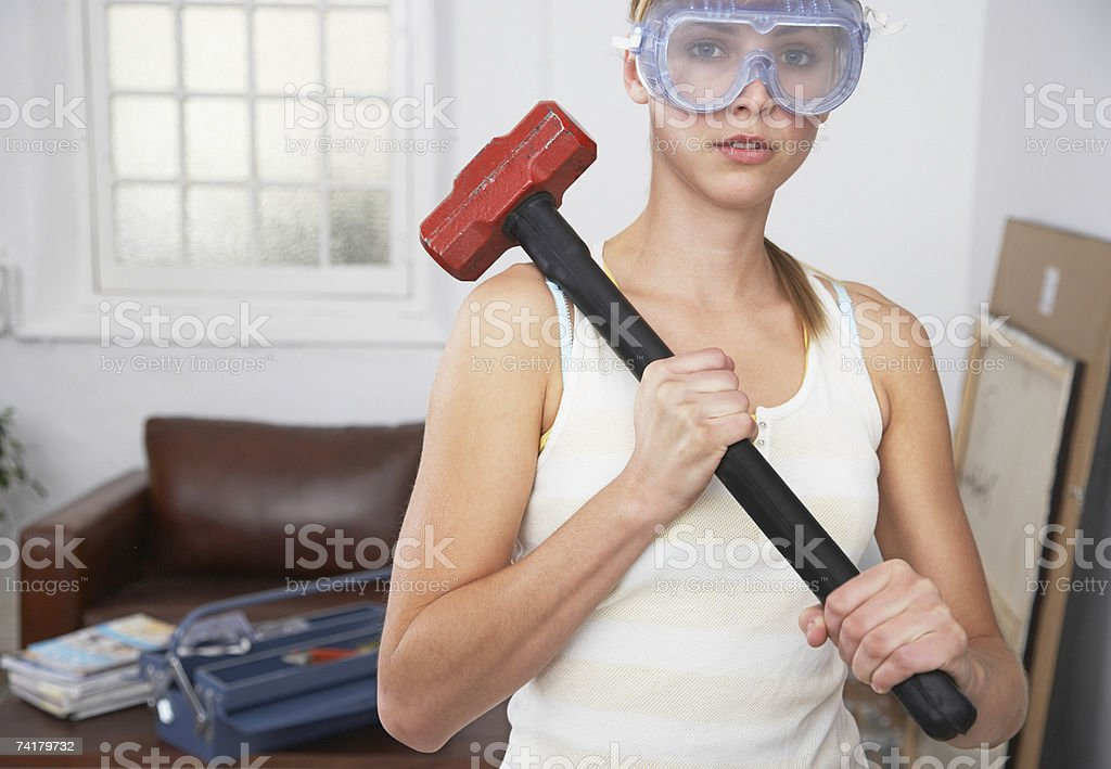 Woman with mallet and eye goggles at home stock photo