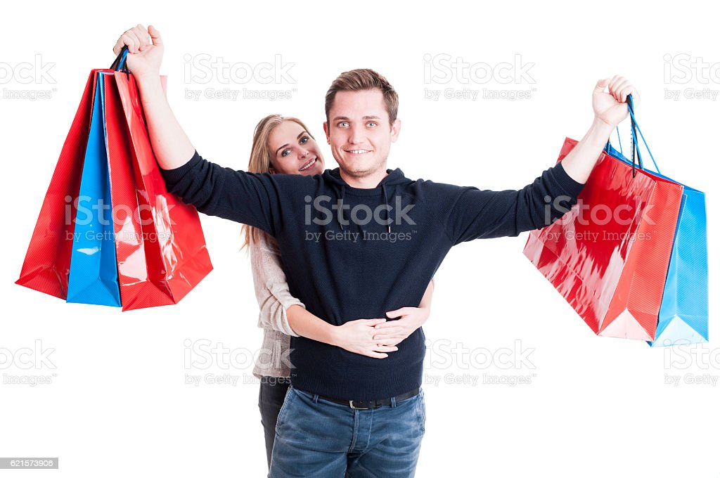 Woman with man holding up bunch of shopping bags photo libre de droits