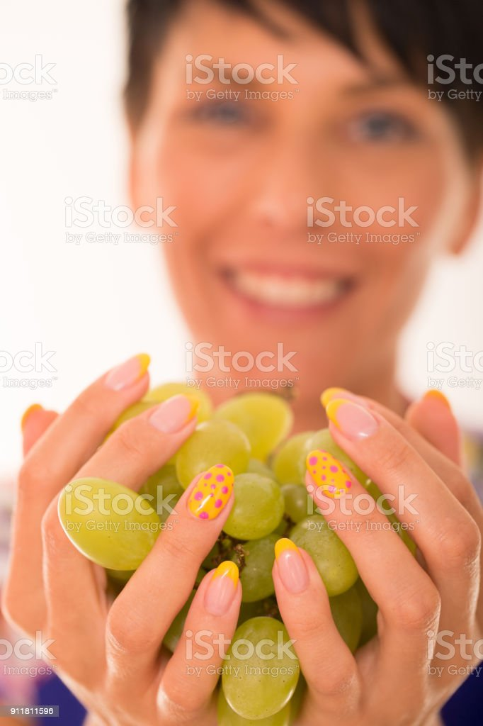 Smiling Woman with Manicured Nails Holding Grape Bunch, Focus on...