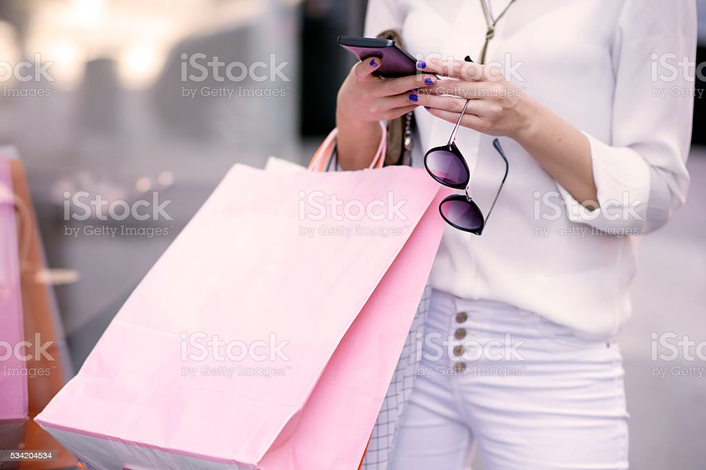 woman with many shopping bags texting stock photo