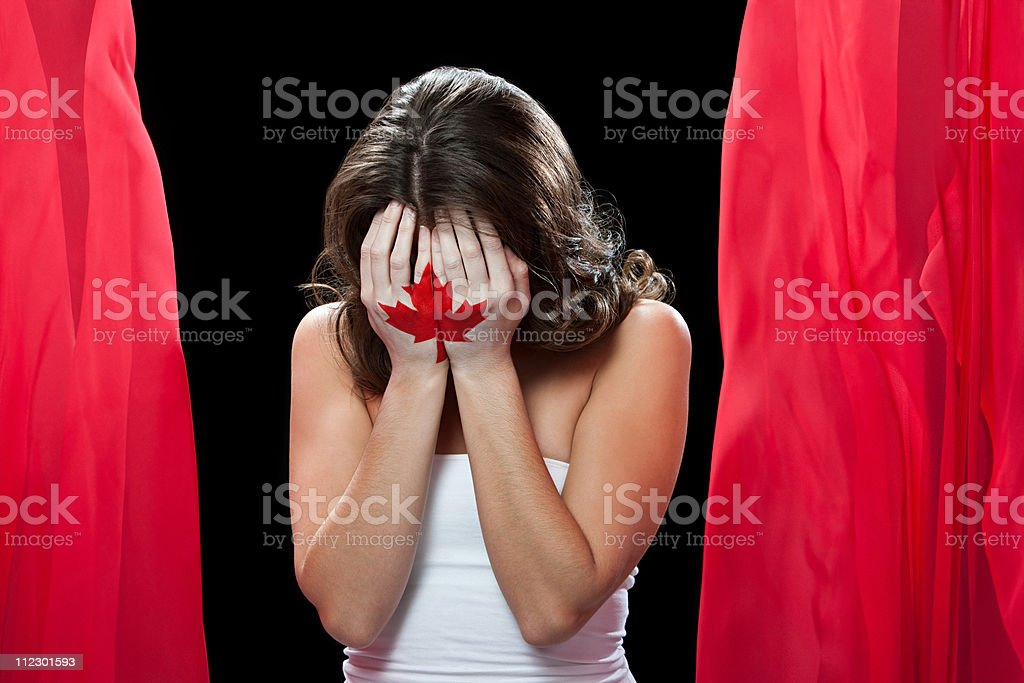 Woman with maple leaf painted on hands, head in hands stock photo