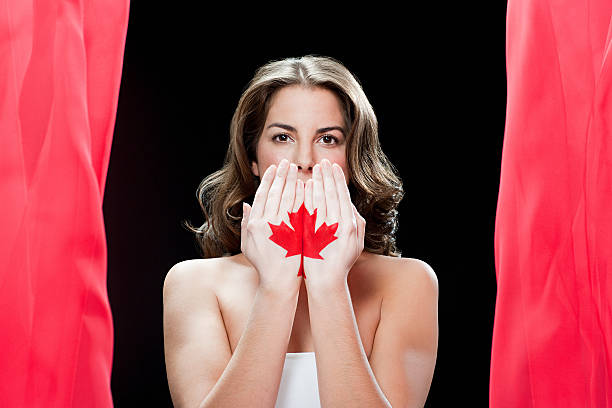 Woman with maple leaf painted on hands stock photo