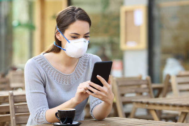 Woman with mask checking news on phone stock photo