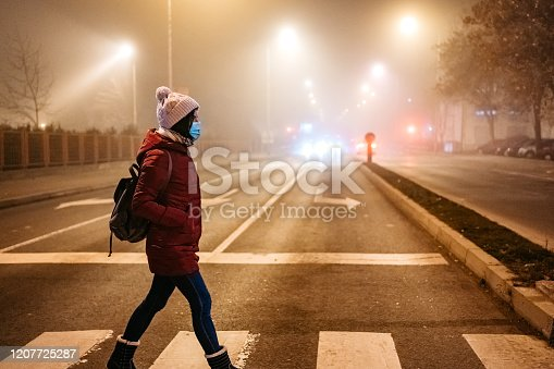 Young woman wearing face mask and crossing the street on pedestrian crossing in foggy night.