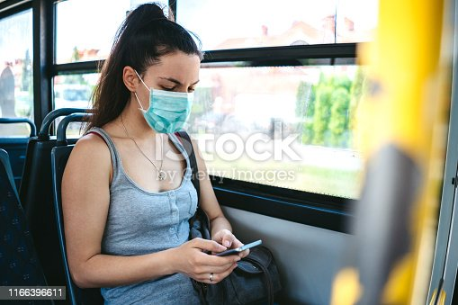 Young caucasian beautiful woman with medical mask taking a bus ride and using her phone while riding.