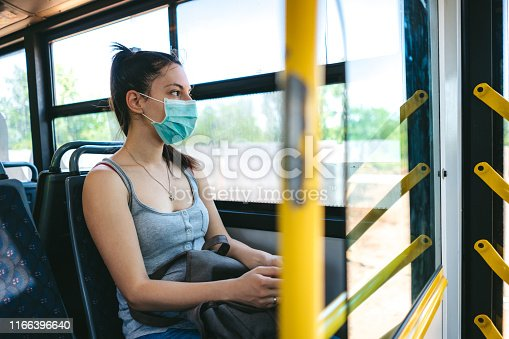 Young caucasian beautiful woman with medical mask taking a bus ride.