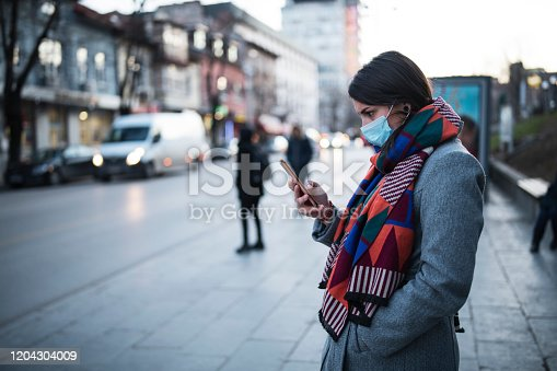Side view of young woman with face protective mask on the street, she waiting for city transport and looking down, she using smartphone.