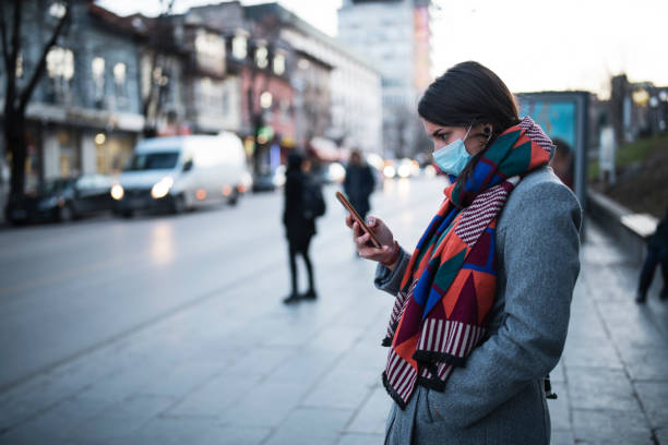 Woman With Mask Using Phone On The Street.