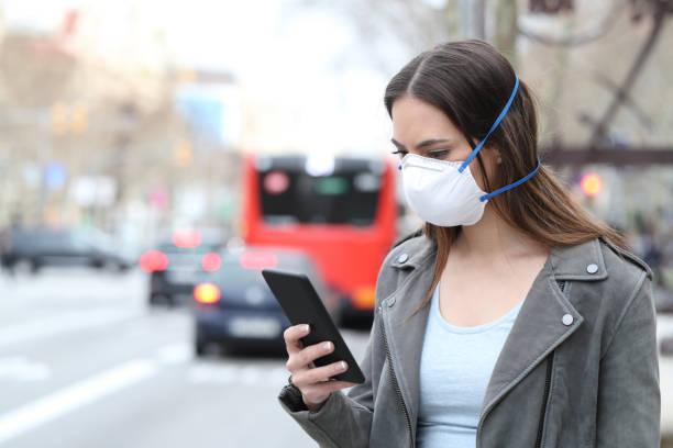 Woman with mask using phone with city traffic background stock photo
