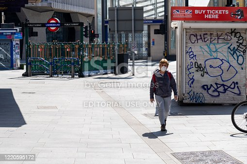 London, UK - April 23rd 2020:  Lady wearing a face mask walking on Tottenham Court Road with London Underground sign in the background and closed entrance during lockdown
