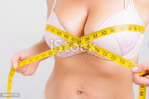 498310066istockphoto Woman with measurement tape around her bust 936007252