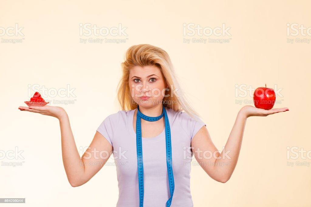 Woman with measuring tape choosing what to eat royalty-free stock photo