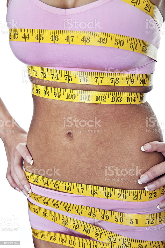 Woman with measuring tape wrapped on her body royalty-free stock photo