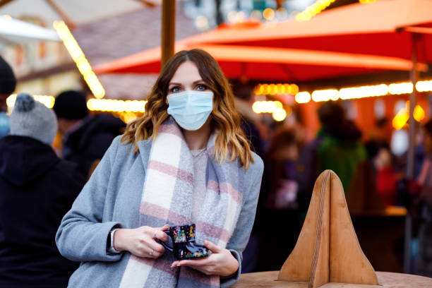 Woman with medical mask drinking hot punch, mulled wine on German Christmas market. People with masks as protection against corona virus. Covid pandemic time in Europe and in the world. stock photo