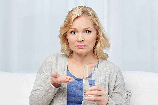 woman with medicine and water glass at home stock photo