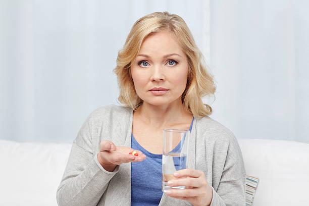 Mujer con medicina y agua de vidrio en el hogar - foto de stock