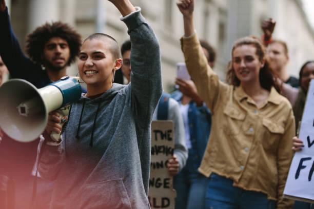 mujer con megáfono durante la protesta callejera - civil rights fotografías e imágenes de stock