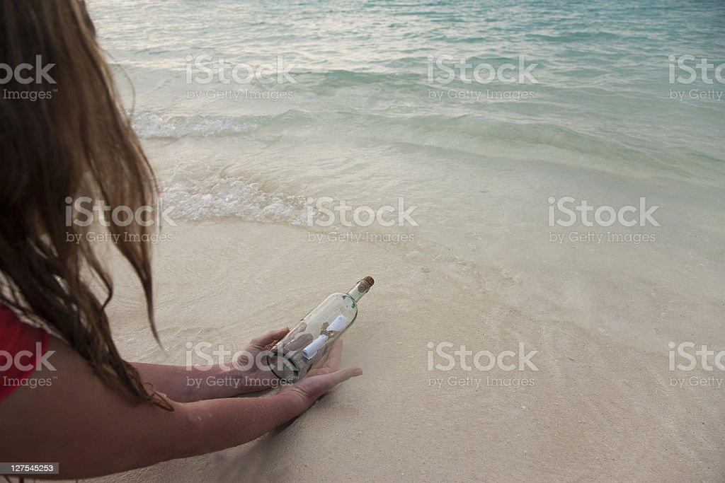 Femme avec message dans une bouteille sur la plage - Photo