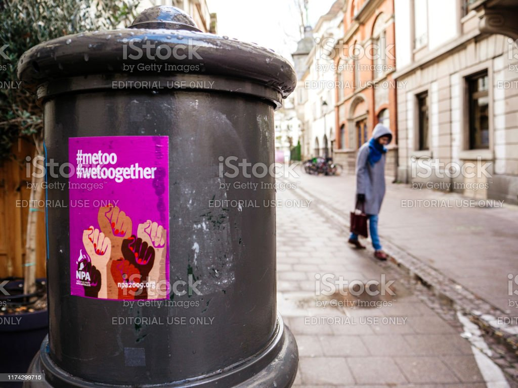 Woman with Metoo wetoogether campaign poster Paris, France - Dec 15, 2017: Single sad woman walking on French street with Metoo wetoogether campaign poster on the steel pillar Adult Stock Photo