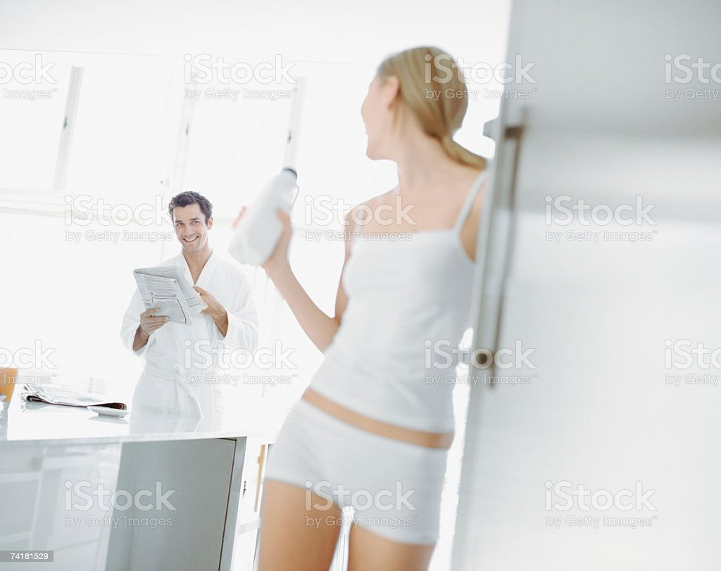 Woman with milk jug and man in robe with newspaper royalty-free stock photo