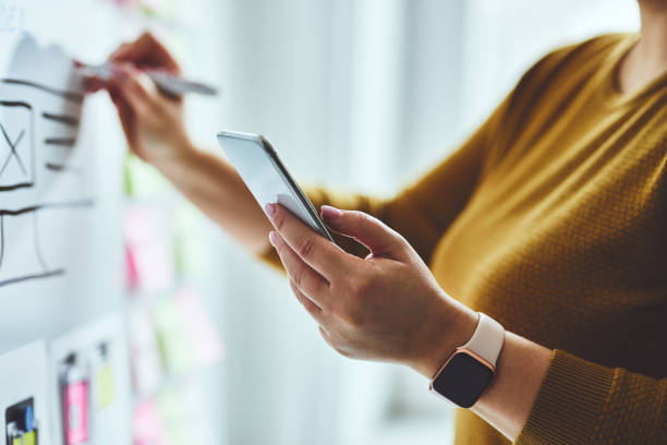 Woman with mobile phone and marker planning website stock photo