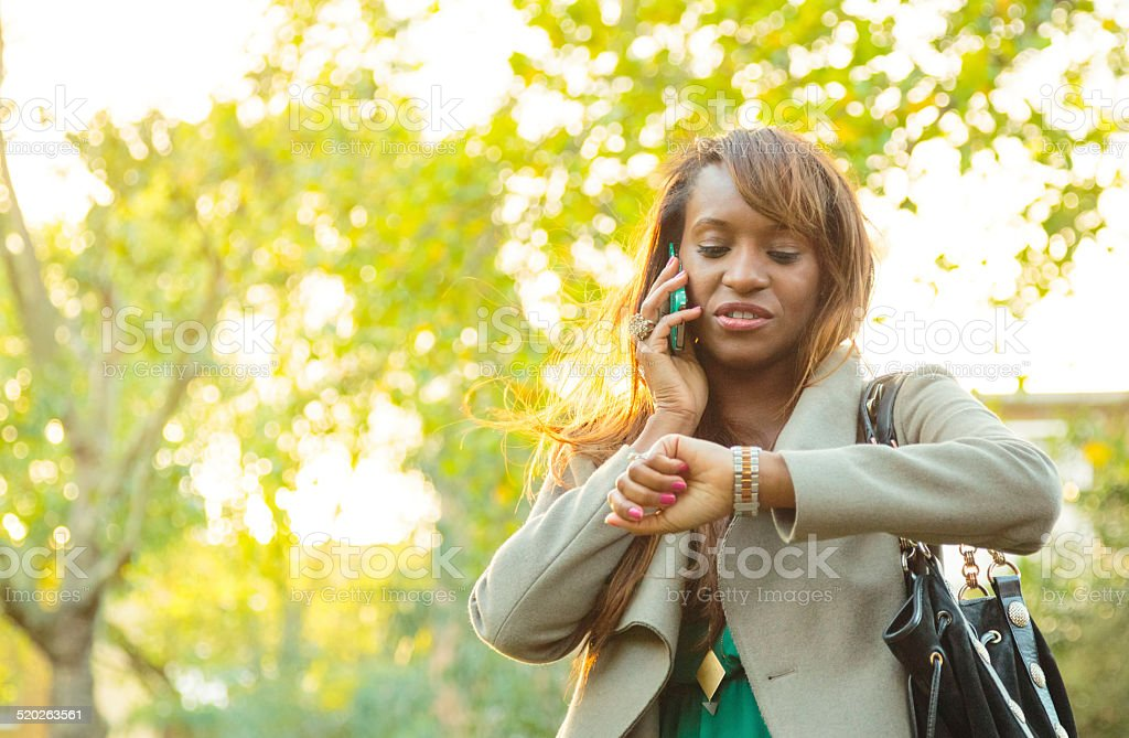 Woman with mobile phone checking the time stock photo