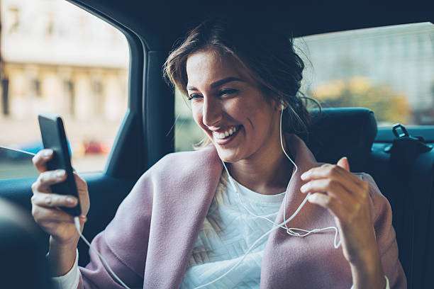 Woman with mobile phone in a car stock photo