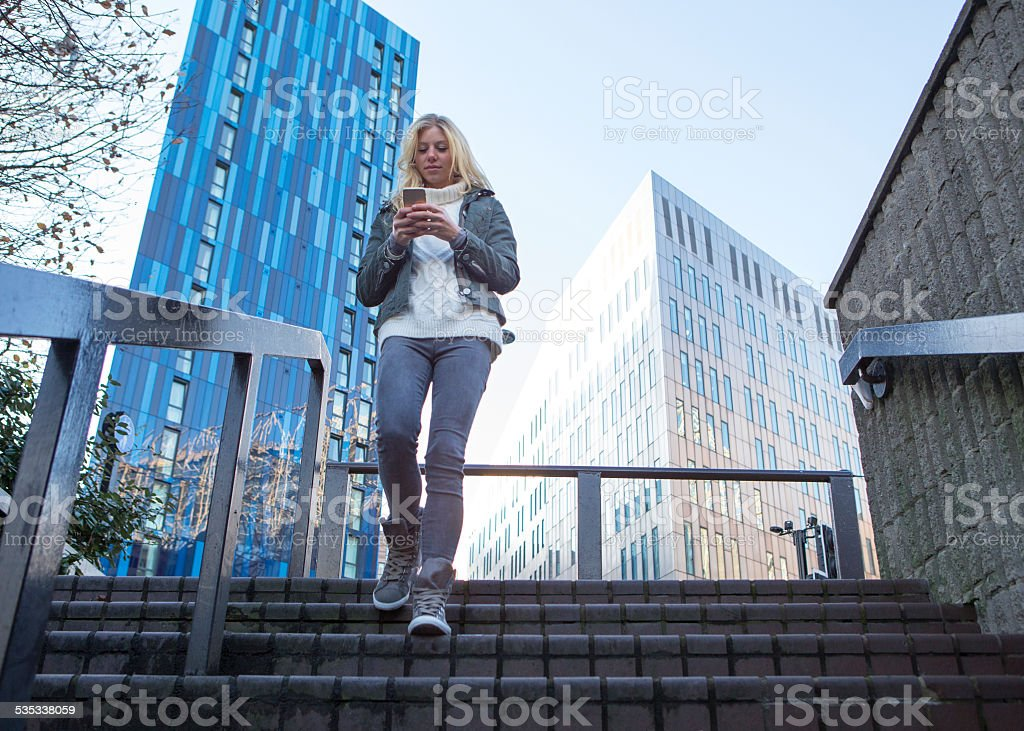 Woman With Mobile Telephone On Stairs stock photo