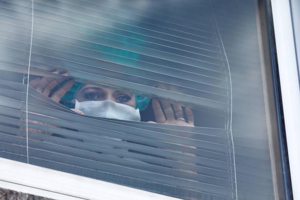 Frau mit Mundschutz schaut durch Jalousien – Foto