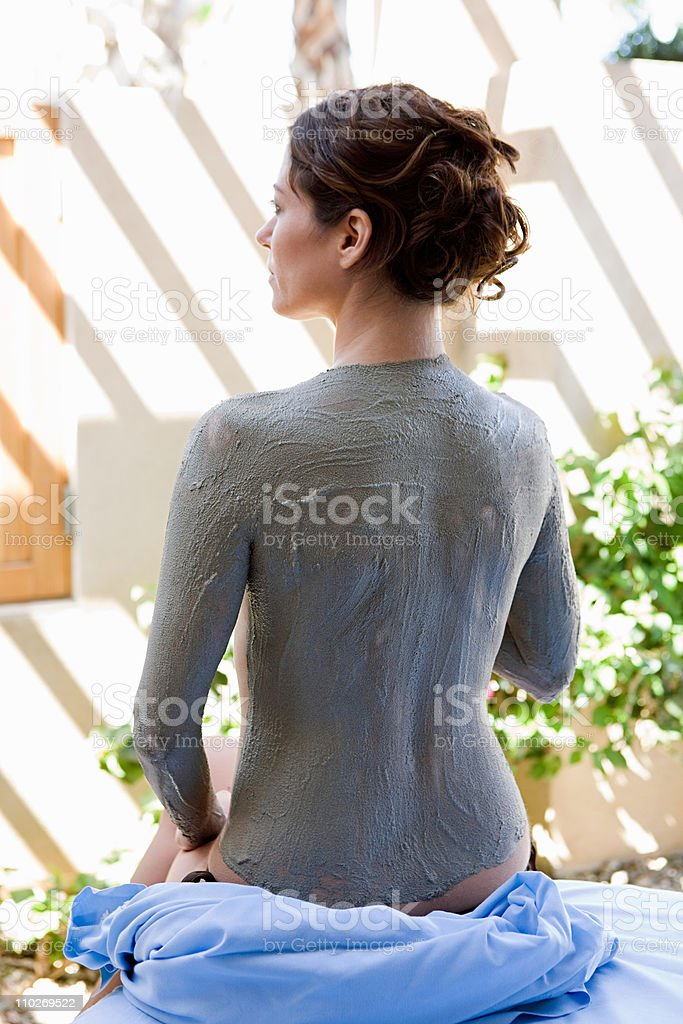 Woman with mud mask on back stock photo