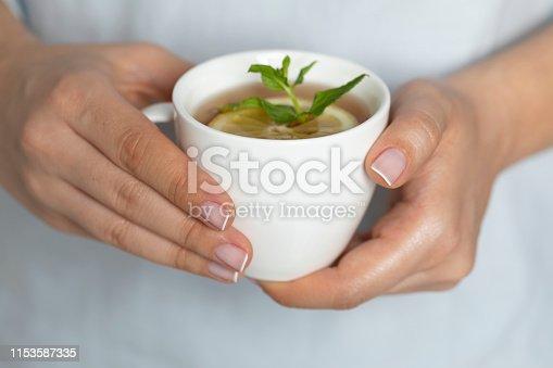Close up woman drinking herbal tea, studio shot.