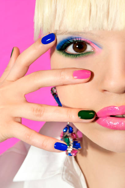 Woman with multi-colored make-up and manicure. Fashionable multi-colored make-up and manicure on a blonde girl on a pink background close-up. pink nail polish stock pictures, royalty-free photos & images