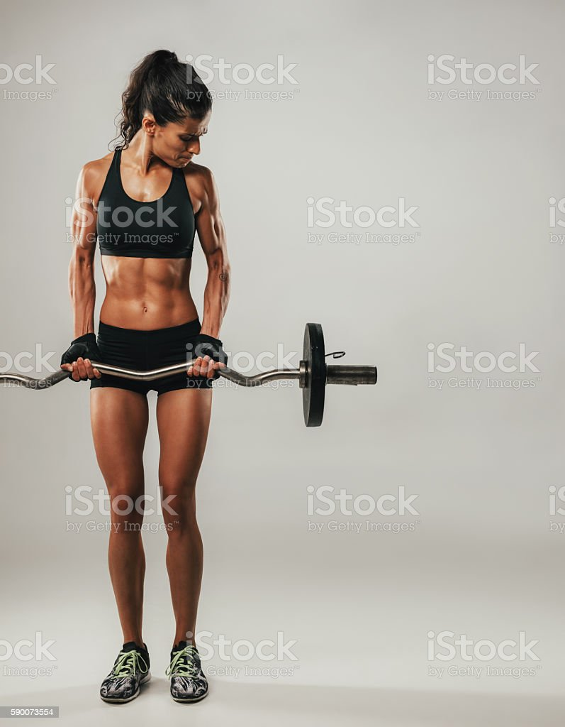 Woman with muscular physique lifting barbell stock photo