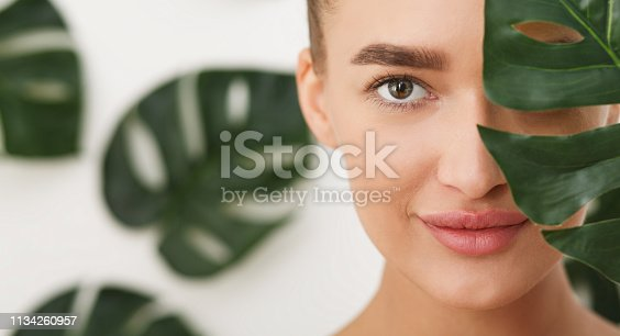 istock Woman with natural make up and green leaf 1134260957