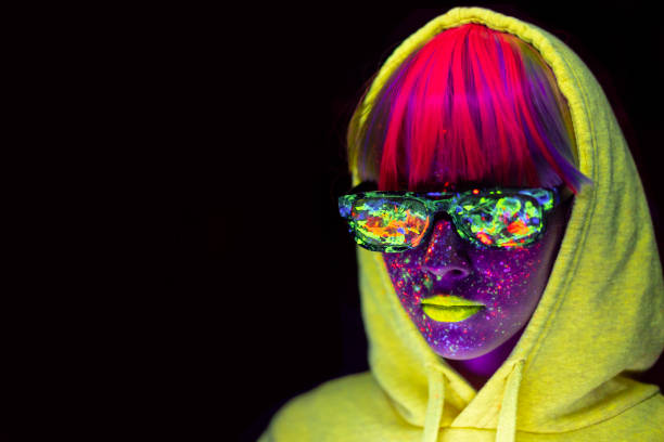 Woman with neon makeup powder on face and clothes, colored sunglasses Woman with neon makeup powder on face in studio. Young woman painted with fluorescent make up. saturated color stock pictures, royalty-free photos & images