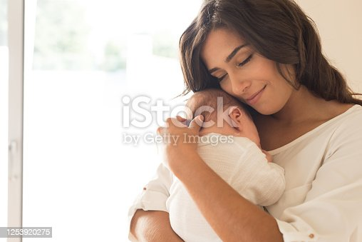 istock Woman with newborn baby 1253920275