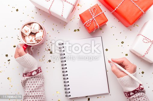 Cozy holidays. Woman with notepad, cacao and Christmas presents on white background, copy space